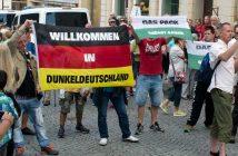 """Mit Deutschlandfahnen """"Willkommen in Dunkeldeutschland"""" und """"Das Pack grüßt Gauck"""" protestieren am 26.06.2016 Menschen gegen Bundespräsident Joachim Gauck beim 116. Deutschen Wandertag auf dem Marktplatz in Sebnitz (Sachsen)."""